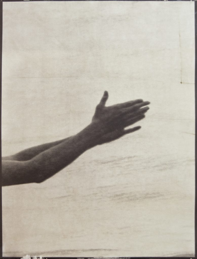 brown image of two hands clapping over water