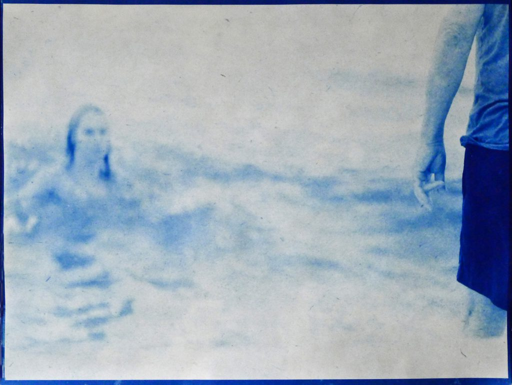 blue image of portion of man standing with faint image of woman's head & shoulders in the distance
