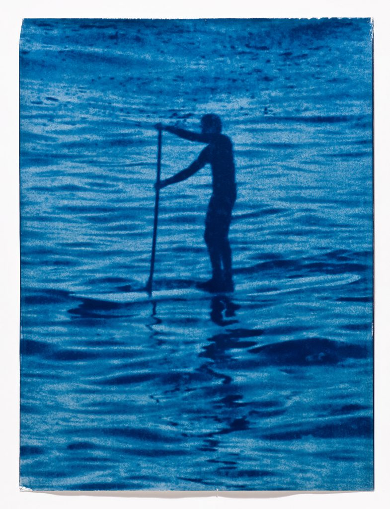 blue silhouette of stand up paddleboard rider