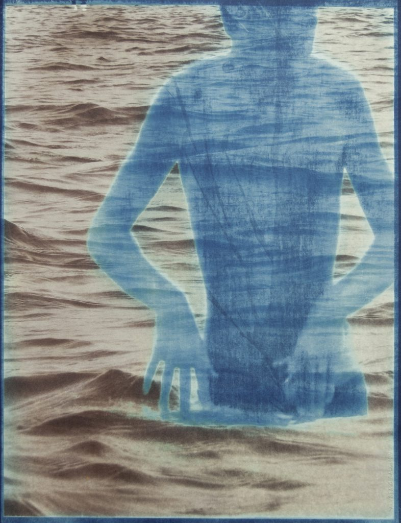 blue & brown image of boy in water with waves