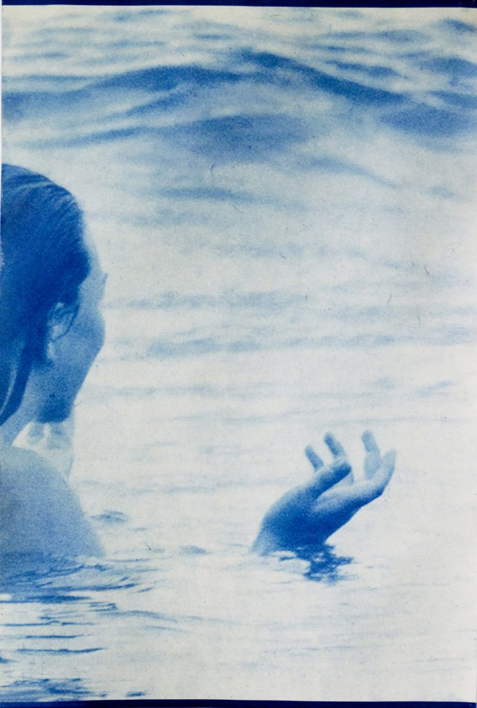 blue image of woman in water with hand raised slightly above surface of water