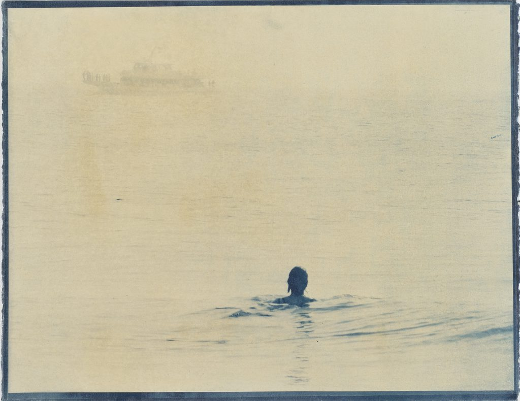 woman in water, with faint image of boat in distance
