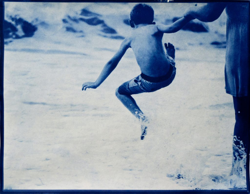 boy leaping above waves, holding mother's hand