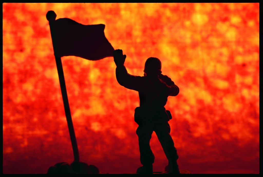 toy soldier with flag against firey background