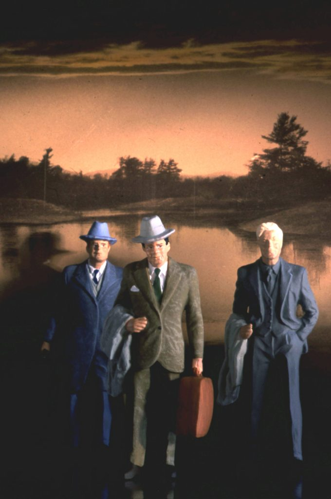 figurines of 3 men in business suits against sunset landscape