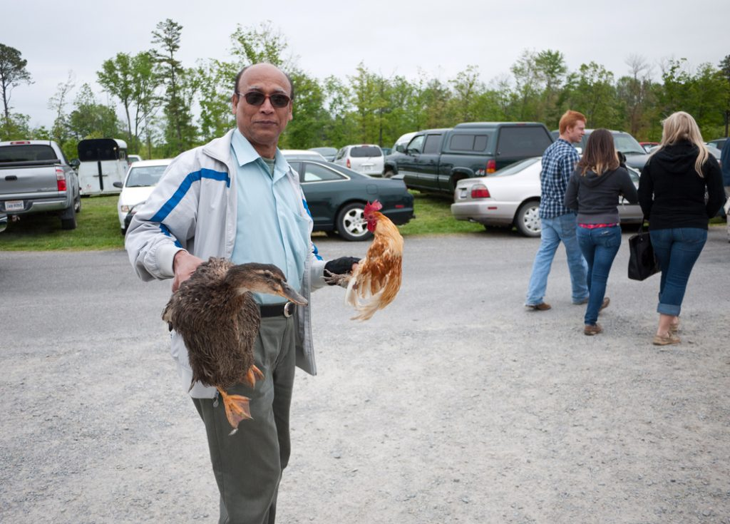 man holding chicken & duck in parking lot